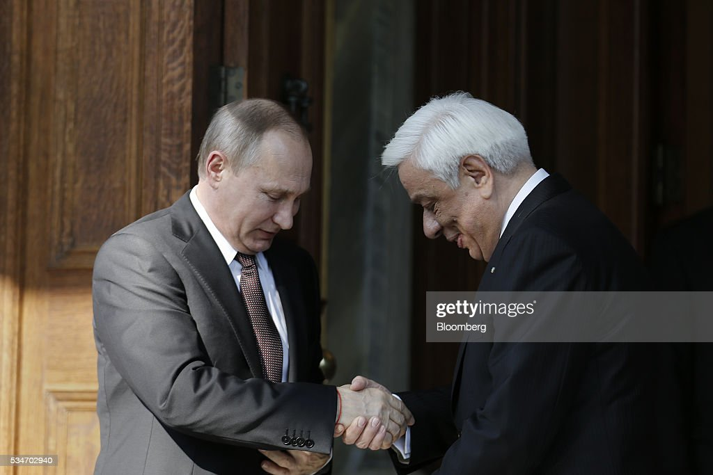 Vladimir Putin, Russia's president, left, shakes hands with Prokopis Pavlopoulos, Greece's president, at the presidential palace in Athens, Greece, on Friday, May 27, 2016. The Russian president is visiting Athens at a time when Greece is turning a page, economic recovery is in prospect, Alexis Tsipras, Greece's prime minister, said in comments at start of meeting. Photographer: Alkis Konstantinidis/Pool via Bloomberg