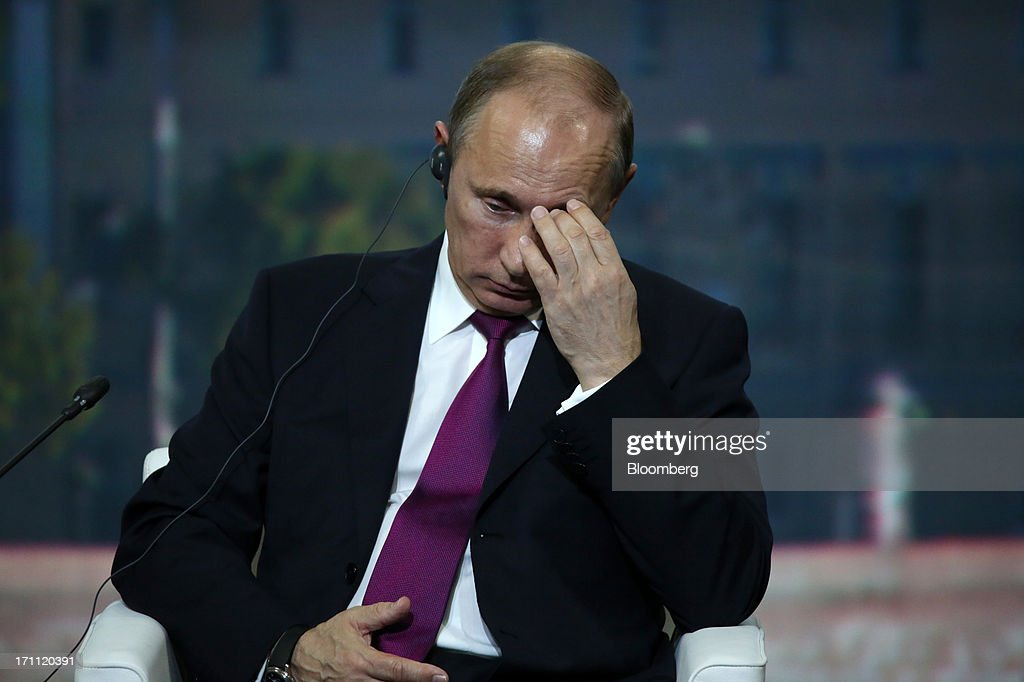 <a gi-track='captionPersonalityLinkClicked' href=/galleries/search?phrase=Vladimir+Putin&family=editorial&specificpeople=154896 ng-click='$event.stopPropagation()'>Vladimir Putin</a>, Russia's president, reacts during a session with Angela Merkel, Germany's chancellor, on day two of the St. Petersburg International Economic Forum 2013 (SPIEF) in St. Petersburg, Russia, on Friday, June 21, 2013. Putin is battling investor skepticism to woo foreign executives descending on his hometown today as Russia's economy faces a risk of recession and a crackdown on critics scares off intellectuals. Photographer: Andrey Rudakov/Bloomberg via Getty Images