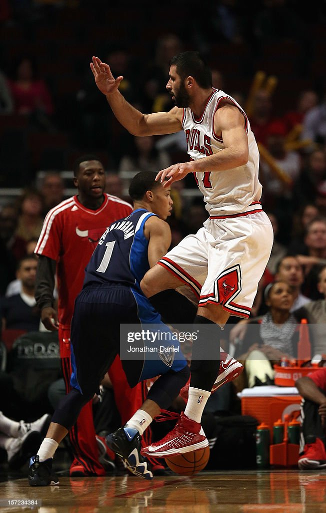 Vladimir Radmanovic #77 of the Chicago Bulls leaps to avoid Jared Cunningham #1 of the Dallas Mavericks at the United Center on November 28, 2012 in Chicago, Illinois. The Bulls defeated the Mavericks 101-78.