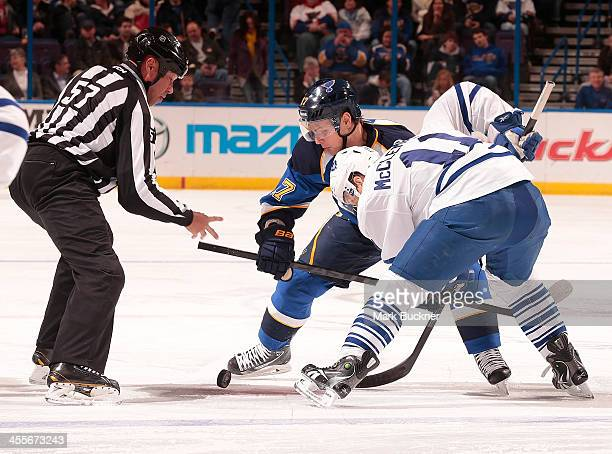 Vladimir Sobotka of the St Louis Blues takes a face off against Jay McClement of the Toronto Maple Leafs as linesman Jay Sharrers drops the puck...