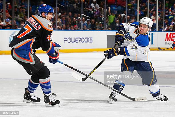 Vladimir Sobotka of the St Louis Blues takes a shot as Andrew MacDonald of the New York Islanders defends him at Nassau Veterans Memorial Coliseum on...