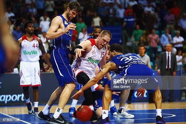 Vladimir Stimac of Muenchen is challenged by Aaron Doornekamp and Justin Cobbs of Frankfurt during the Beko Basketball Bundesliga play off match...