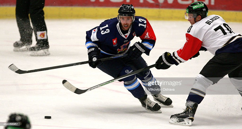 Vladimir Svacina of Vitkovice Ostrava eyes the puck under pressure from #70 Yannick Blaser of EV Zug during the Champions Hockey League group stage game between Vitkovice Ostrave and EV Zug on August 23, 2014 in Ostrava, Czech Republic.