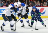 Vladimir Tarasenko and David Backes of the St Louis Blues look on as Jordan Schroeder of the Vancouver Canucks skates up ice with the puck during...