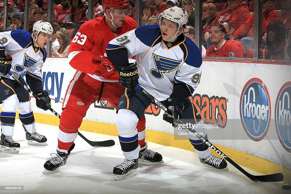 Vladimir Tarasenko #91 of the St. Louis Blues handles the puck in the corner as Joakim Andersson #63 of the Detroit Red Wings defends him during a NHL game at Joe Louis Arena on April 7, 2013 in Detroit, Michigan.