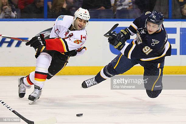 Vladimir Tarasenko of the St Louis Blues takes a shot on goal as he fall to the ice against Mark Giordano of the Calgary Flames during the third...