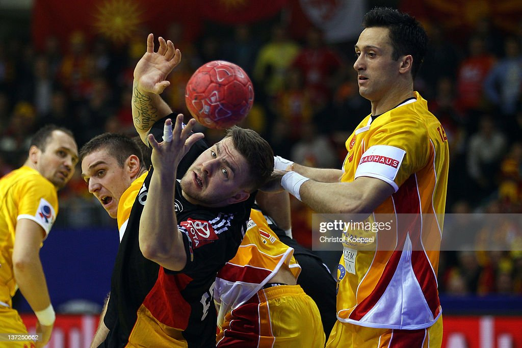 Vladimir Temelkov of Macedonia (R) challenges Christoph Theuerkauf of Germany (L) during the Men's European Handball Championship group B match between Macedonia and Germany at Cair Sports Centre on January 17, 2011 in Nis, Serbia.