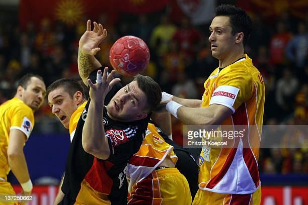 Vladimir Temelkov of Macedonia challenges Christoph Theuerkauf of Germany during the Men's European Handball Championship group B match between...