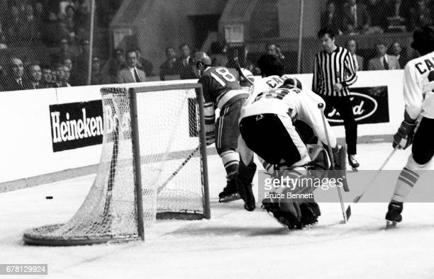 Vladimir Vikulov of the Soviet Union goes for the puck as goalie Ken Dryden of Canada defends the net during a game in the 1972 Summit Series circa...