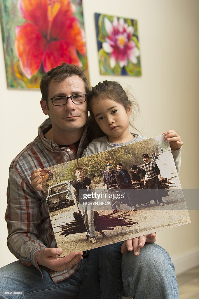 Vladimir Vrnoga and his daughter Vanessa hold an old photograph of himself, taken by AFP photographer Patrick Baz 20 years ago in Sarajevo, December 16, 2012 at his home in Chico, California. Twenty years have passed since Vrnoga served three hard years in the Bosnian and fled to the United States. He now lives with his mother, his wife and three year old daughter in Chico, north of San Francisco, where he is employed by a large beverage manufacturer.
