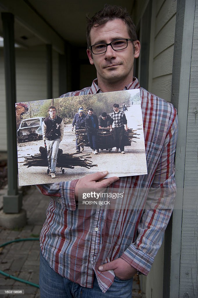 Vladimir Vrnoga holds an old photograph of himself, taken by AFP photographer Patrick Baz 20 years ago in Sarajevo, December 16, 2012 at his home in Chico, California. Twenty years have passed since Vrnoga served three hard years in the Bosnian and fled to the United States. He now lives with his mother, his wife and three year old daughter in Chico, north of San Francisco, where he is employed by a large beverage manufacturer.