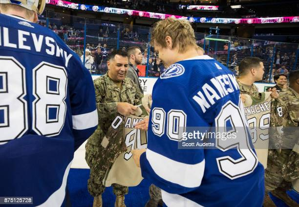 Vladislav Namestnikov of the Tampa Bay Lightning signs a jersey for a member of the military after the win against the Dallas Stars at Amalie Arena...