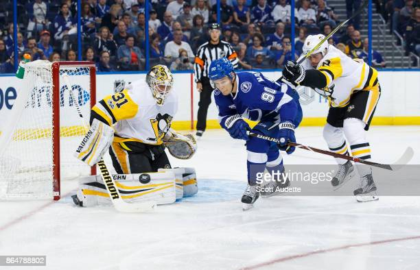 Vladislav Namestnikov of the Tampa Bay Lightning skates against goalie Antti Niemi and Brian Dumoulin of the Pittsburgh Penguins during the first...