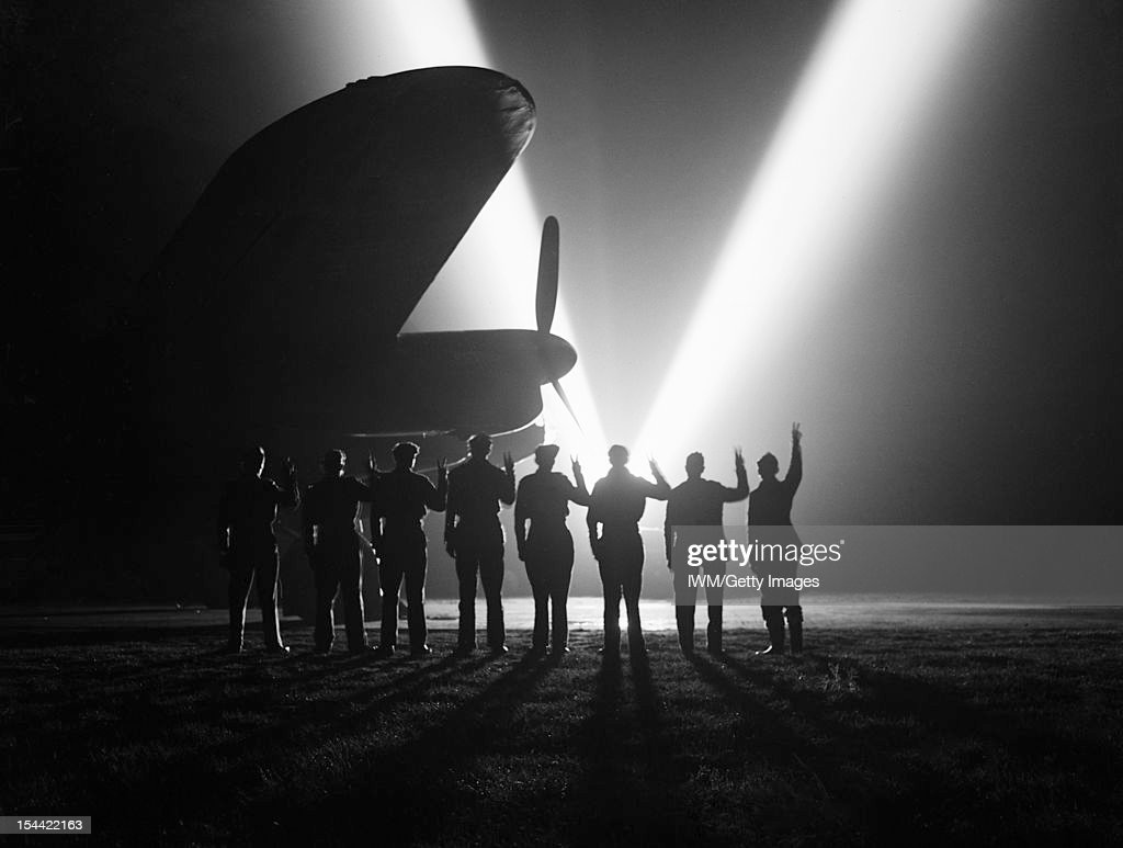 V-Lights Go Up, Ground crew on a RAF Bomber Command station in Britain return the V-sign to a neighbouring searchlight crew . Silhouetted is the nose of a Lancaster, May 1945.