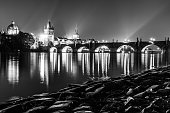 Vltava River and Charles Bridge with Old Town Bridge Tower by night, Prague, Czechia. UNESCO World Heritage Site. Black and white image.