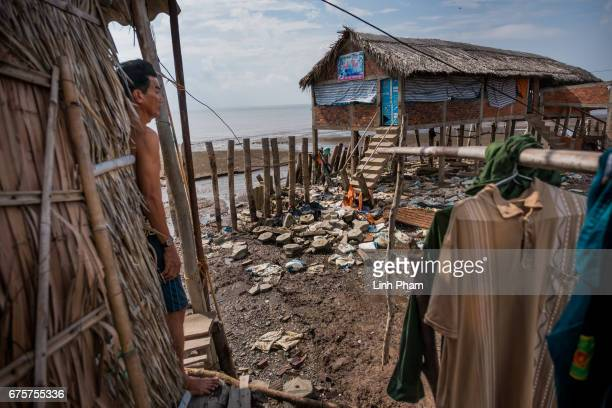 Vo Van Phuong looks at his neighbor's destroyed cafe from his clam guard hut next to the seafront on April 29 2017 in Bao Thuan Village Ba Tri...