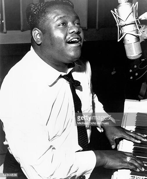 B vocalist Fats Domino plays piano while singing into a vintage microphone in circa 1958