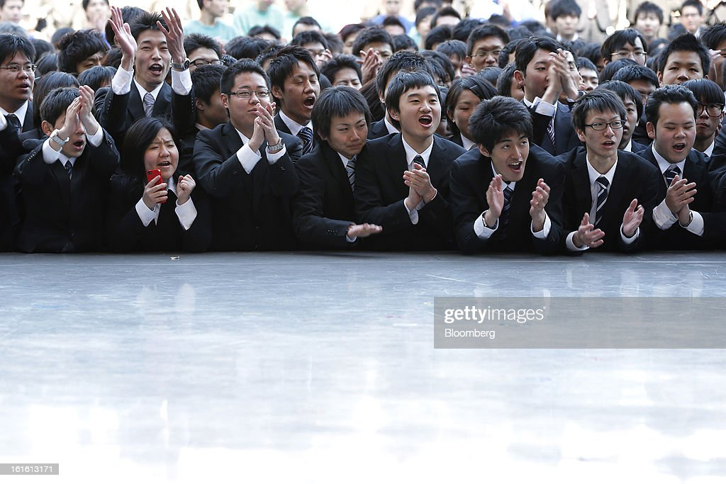 Vocational students cheer and applaud in front of a stage during a rally to start off job-hunting in Tokyo, Japan, on Wednesday, Feb. 13, 2013. Shinzo Abe's government announced 10.3 trillion yen in spending last month, which it predicts will increase gross domestic product by about 2 percentage points and create about 600,000 jobs. Photographer: Kiyoshi Ota/Bloomberg via Getty Images