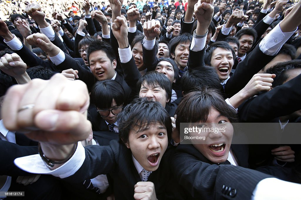 Vocational students raise their fists during a rally to start off job-hunting in Tokyo, Japan, on Wednesday, Feb. 13, 2013. Shinzo Abe's government announced 10.3 trillion yen in spending last month, which it predicts will increase gross domestic product by about 2 percentage points and create about 600,000 jobs. Photographer: Kiyoshi Ota/Bloomberg via Getty Images