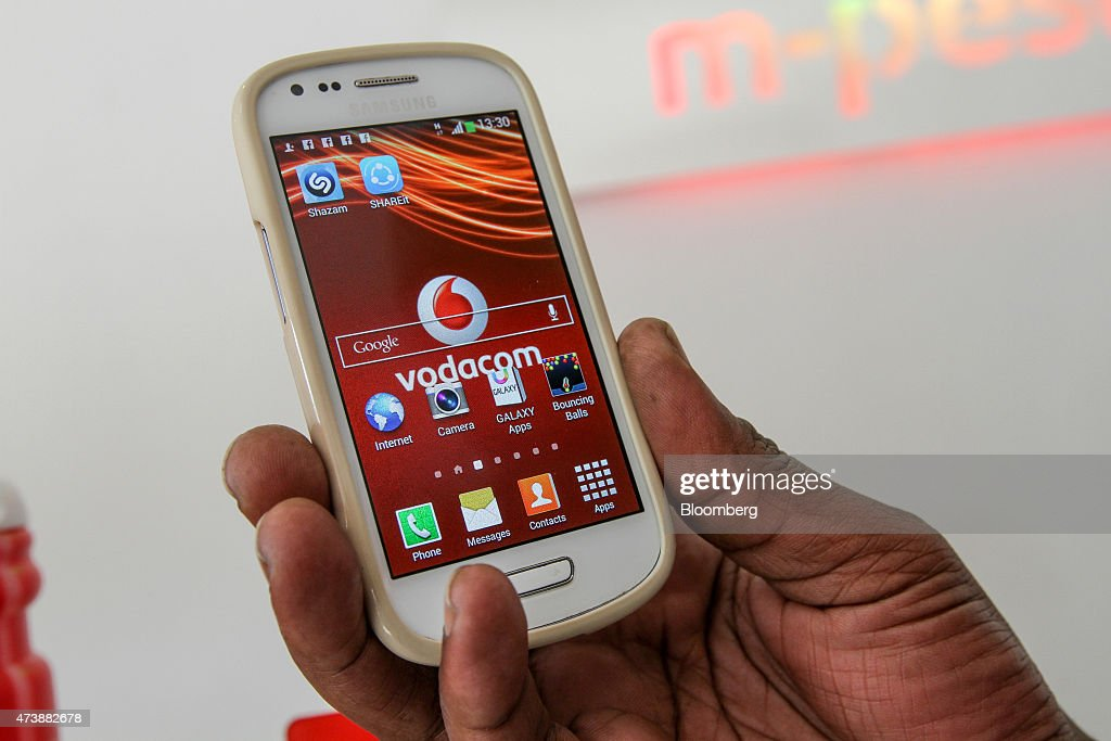 A Vodacom branded smartphone manufactured by Samsung Electronics Co is arranged for a photograph at a phone store operated by Vodacom Group Ltd in...