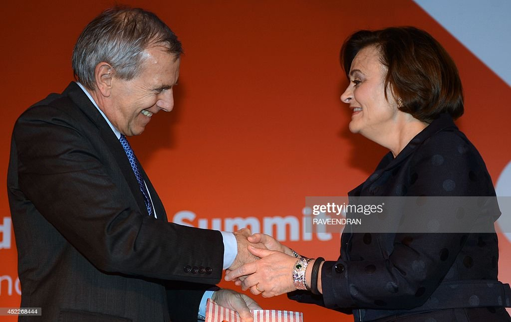 Vodafone CEO and Managing Director, Marten Pieters (L) and founder of the Cherie Blair Foundation for Women, Cherie Blair shake hands during the launch the Vodafaone Connected Women report 2014 in New Delhi on July 17, 2014. The Vodafone Connected Women report has found that providing women with greater access to mobile phones and services could lead to a 29 billion dollar increase in annual global productivity from 2020, as a result of geater female participation in the workforce and saving in public services.