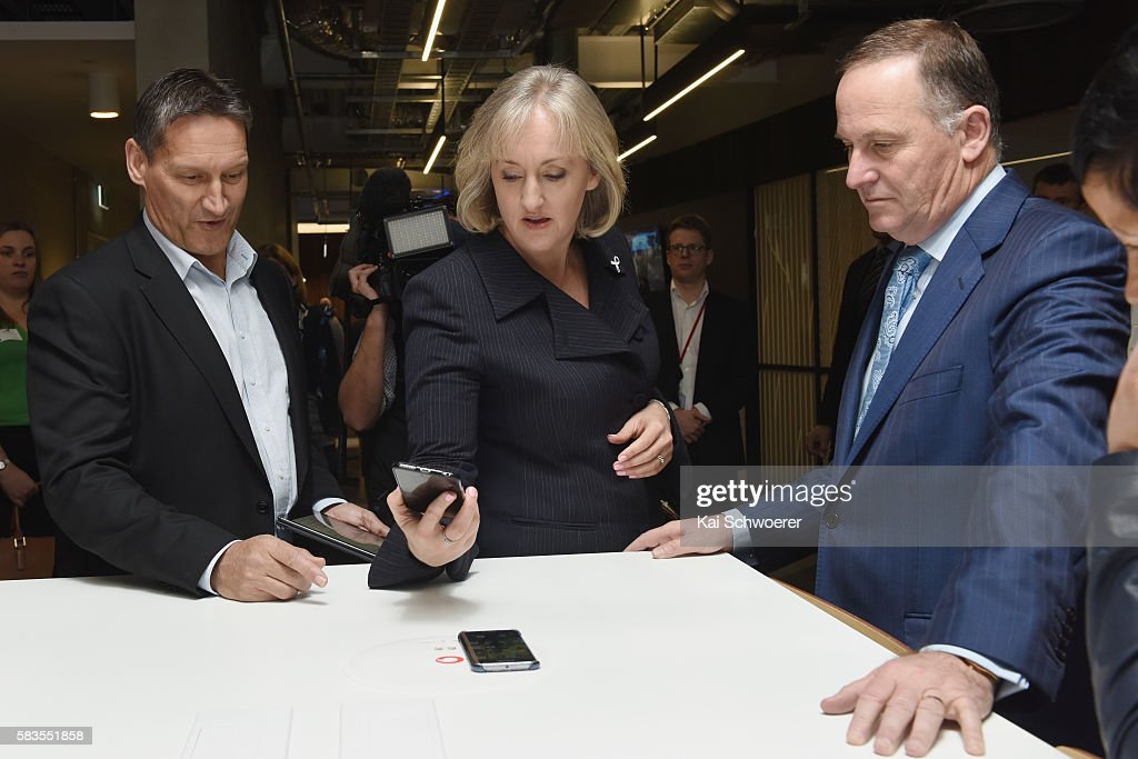 Vodafone CEO Russell Stanners Communications Minister Amy Adams and Prime Minister John Key try a new smartphone charger during the grand opening of...