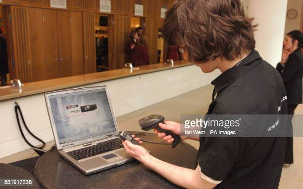 A vodafone employee scans a barcode from a text message ticket for Snow Patrol during their exclusive one off gig at The Royal Opera House central...