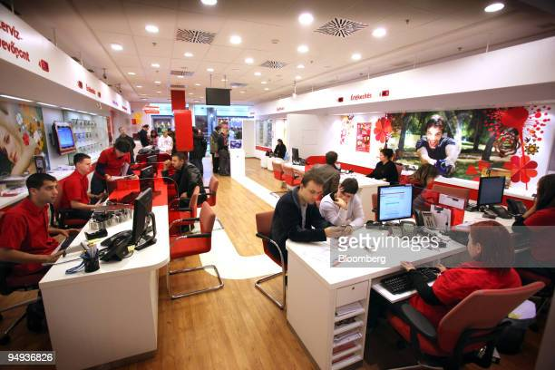 Vodafone employees sit with customers at the Vodafone store in Budapest Hungary on Saturday Jan 31 2009 Vodafone Group Plc the world's largest...