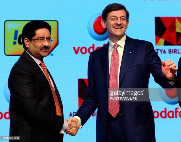 Vodafone Group CEO Vittorio Colao shakes hand with chairman of India's Aditya Birla Group Kumar Mangalam Birla during a news conference in Mumbai on...