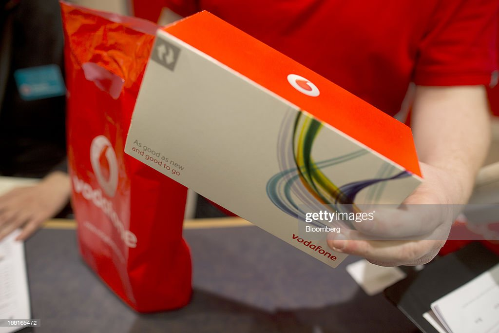 A Vodafone Group Plc employee holds a boxed handset for a photograph at the company's Oxford Street store in London, U.K., on Monday, April 8, 2013. Vodafone Group Plc is restating its results going back two fiscal years as new international accounting rules for joint ventures cut historical revenue and earnings. Photographer: Simon Dawson/Bloomberg via Getty Images