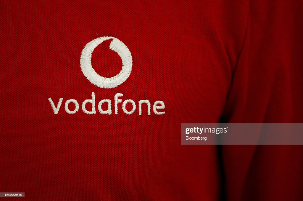 A Vodafone Group Plc logo is seen on an employee's work shirt inside a company store in Barcelona, Spain, on Tuesday, Jan. 15, 2013. Vodafone Group Plc, the world's second largest mobile-phone company, plans to reduce the workforce at its Spanish unit as unemployment exceeding 25 percent in the recession-plagued country causes sales to drop. Photographer: David Ramos/Bloomberg via Getty Images