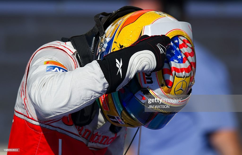 Vodafone McLaren Mercedes driver Lewis Hamilton of Britain points to his helmet as he exits his car in the pits after winning the United States Formula One Grand Prix at the Circuit of the Americas on November 17, 2012 in Austin, Texas. A bold passing maneuver at the end of a long straightway slipped Hamilton past Sebastian Vettel of Team Red Bull Racing allowing Hamilton on to win the US Grand Prix in the first Formula One race on American soil since 2007. AFP PHOTO/Jim WATSON