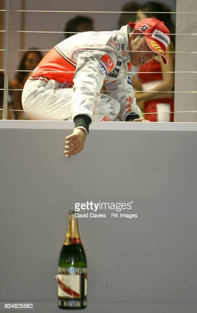 Vodafone McLaren Mercedes' Lewis Hamilton drops his magnum of champagne from the podium after coming third in the Singapore Grand Prix