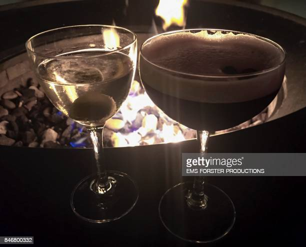 Vodka Martini and Martini Espresso cocktails in front of burning flames during night