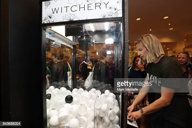 Vogue Senior Fashion Editor Kate Darvill has a go on the skill tester claw machine at Witchery in David Jones during Vogue American Express Fashion's...