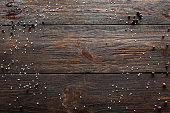 Void wooden background of cutting board with wooden texture and scattered spices on it. Top view on void wooden background with pepper and salt.