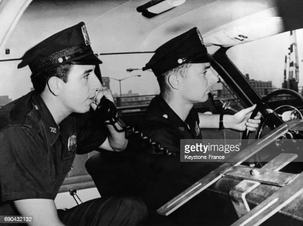 Voiture de police équipée d'un ordinateur recevant des télétypes en temps réel et d'un téléphone permettant la communication entre les équipes afin...