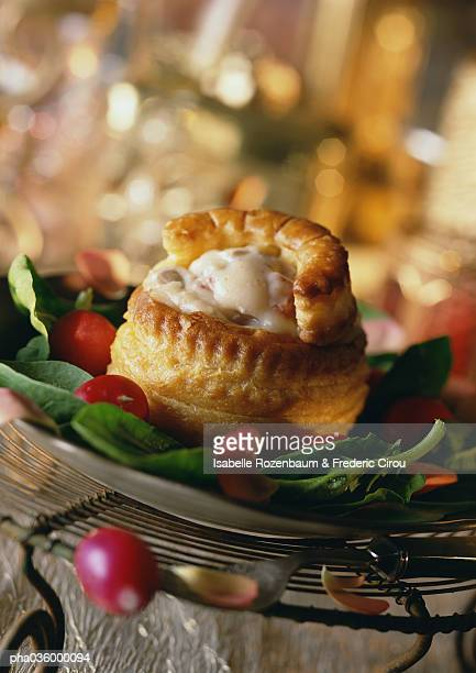 Vol-au-vent (french pastry with savory filling), on bed of greens, close-up