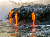 Sea view of Kilauea Volcano in Big Island, Hawaii, United States. A restless volcano that has been in business since 1983. Shot taken at sunset when the lava glows in the dark as jumps into the sea.