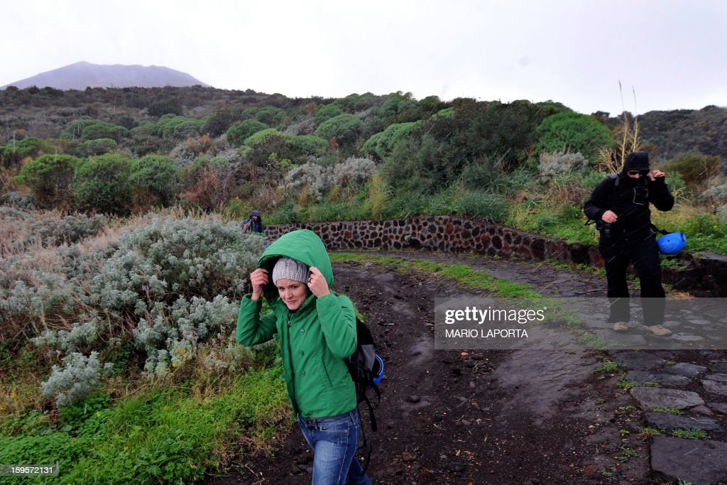 Volcanologists are on their way to the top of the Stromboli volcano, under heavy rain, on the Italian island of Stromboli, on January 16, 2013 after one of Europe's most active volanoes churned into activity. Stromboli, which attracts up to 6.000 tourists every year, had recently been placed under heightened surveillance after scientists registered higher seismic readings. AFP PHOTO/ MARIO LAPORTA