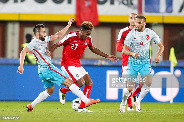 Volkan Sen and Cenk Tosun of Turkey compete for the ball with David Alaba of Austria during the international friendly match between Austria and...