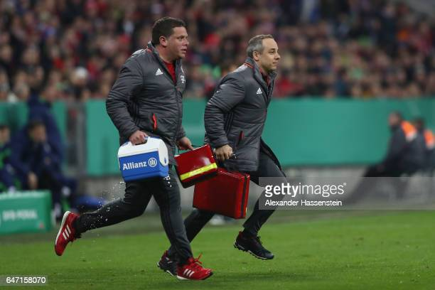 Volker Braun team Doctor of Bayern Muenchen runs with Christian Huhn Physiotherapist of Bayern Muenchen during the DFB Cup quarter final between...