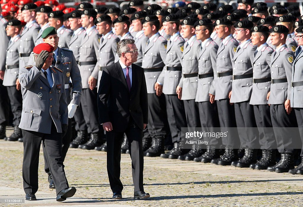 Volker Wieker, chief of staff (Generalinspekteur) of the Bundeswehr (L), and German Defense Minister Thomas de Maiziere review new German Bundeswehr soldiers during a swearing-in ceremony for new recruits of the Bundeswehr, the armed forces of the Federal Republic of Germany, in front of the Reichstag building on July 20, 2013 in Berlin, Germany. In the annual ceremony, new soldiers take office on the anniversary of the assassination attempt on Adolf Hitler by Claus Schenk Graf von Stauffenberg.