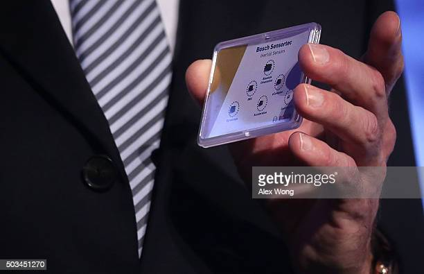 Volkmar Denner Chairman of Board of Management and CEO of Bosch hold up a MEMS Sensors portfolio for consumer electronic devices during a press event...