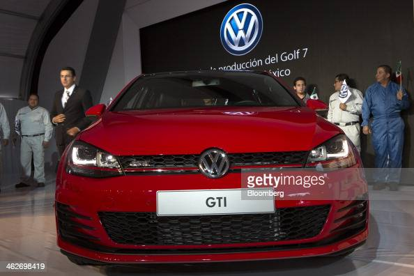 Volkswagen AG factory workers stand behind a new Golf GTI vehicle displayed at a Volkswagen 50th anniversary event at the company's factory in Puebla...
