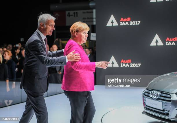 Volkswagen chairman Matthias Mueller escorts German Chancellor Angela Merkel to the booth of Audi at the Internationale Automobil Ausstellung auto...