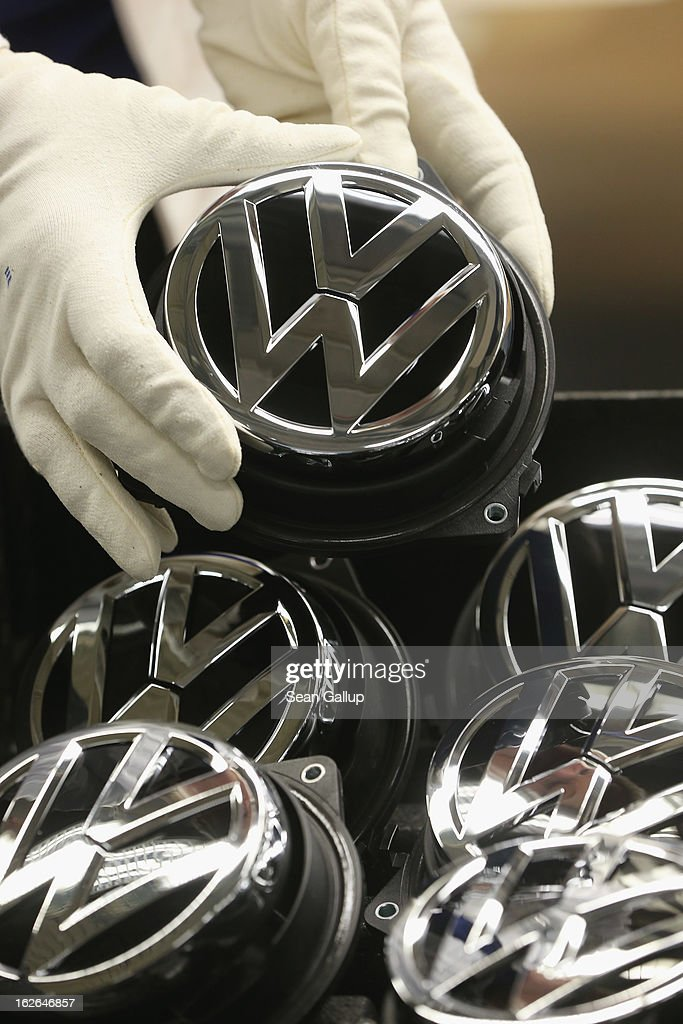 A Volkswagen employee, at the request of photographers, holds a Volkswagen trunk ornament bearing the VW logo at the Golf VII assembly line at the Volkswagen factory on February 25, 2013 in Wolfsburg, Germany. Volkswagen will announce financial results for 2012 on March 14.