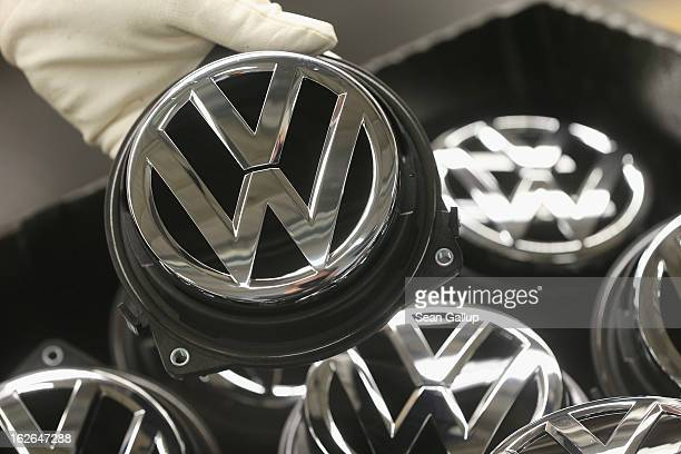 Volkswagen employee at the request of photographers holds a Volkswagen trunk ornament bearing the VW logo at the Golf VII assembly line at the...