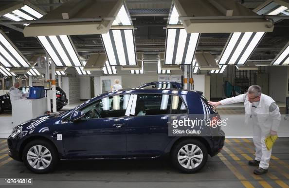Volkswagen employee does a final check on a new VW Golf VII car at the Volkswagen factory on February 25 2013 in Wolfsburg Germany Volkswagen will...
