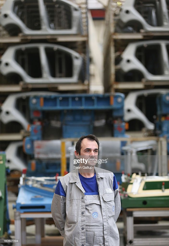 A Volkswagen employee stands near stamped car body parts for new VW Golf VII and Tiguan cars at the Volkswagen factory on February 25, 2013 in Wolfsburg, Germany. Volkswagen will announce financial results for 2012 on March 14.